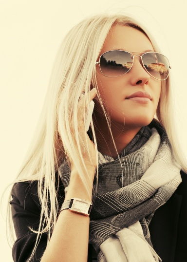 Blond fashion business woman in sunglasses calling on cell phone outdoor