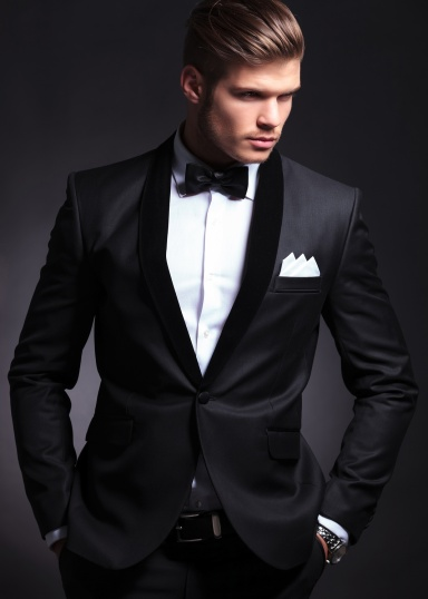 waist-up picture of an elegant young fashion man in tuxedo looking away from the camera while holding hands in pockets.on black background